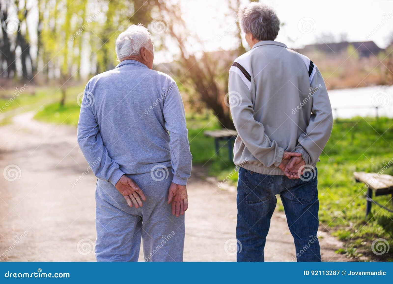 Взгляд от заднего взрослого сына идя с его старшим отцом