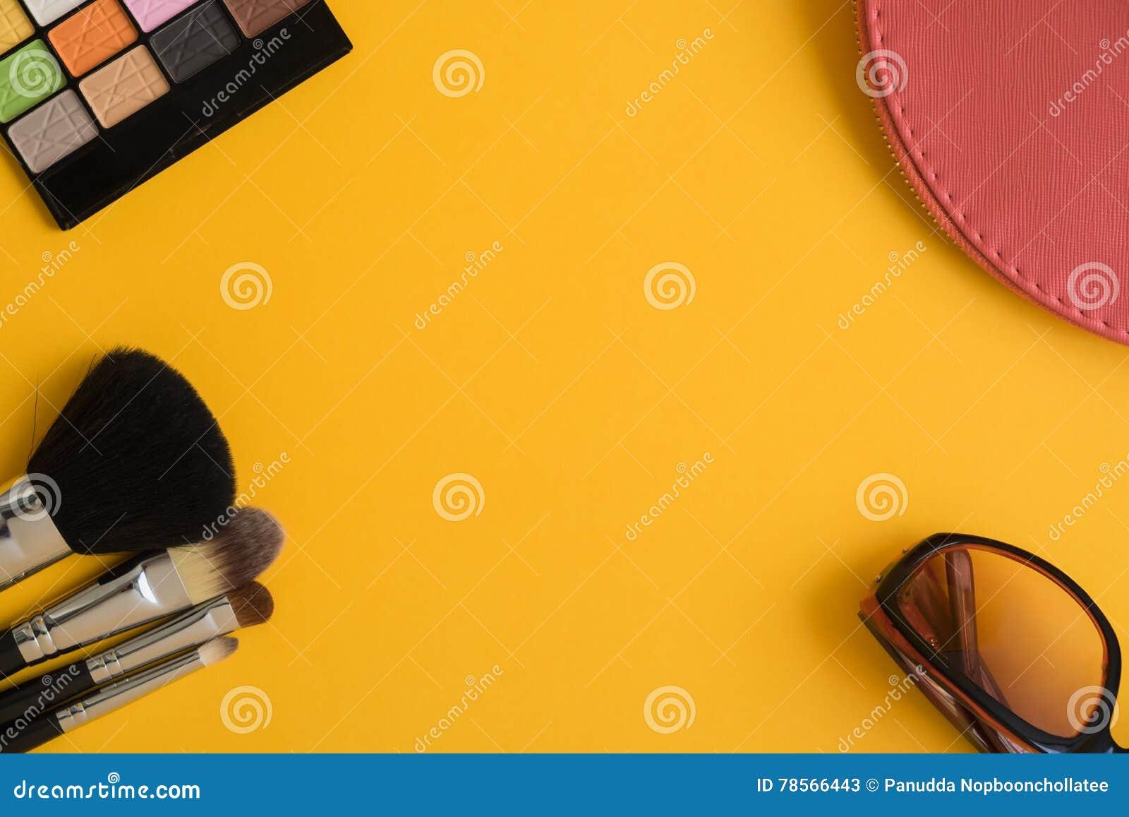 Взгляд сверху деталей косметик на желтой предпосылке