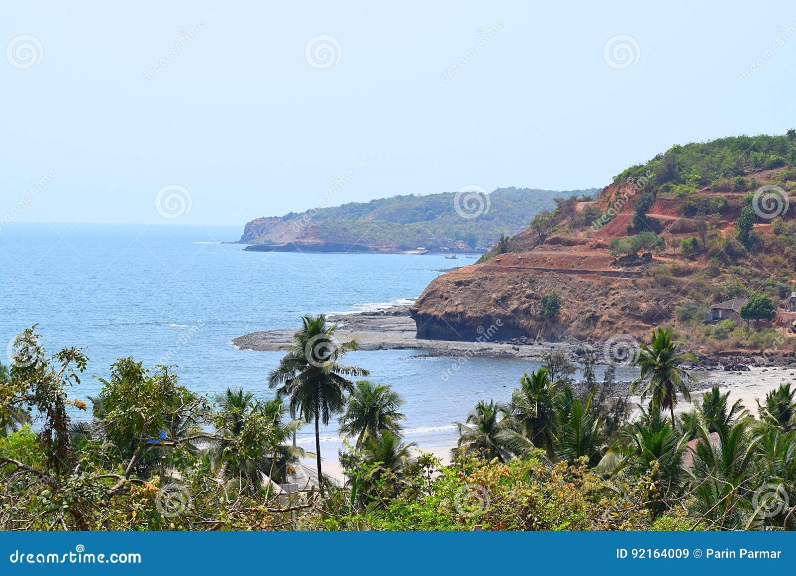 Взморье Аравийского моря с холмами и пальмами, пляжем Velaneshwar, Ratnagiri, махарастрой, Индией - естественной предпосылкой