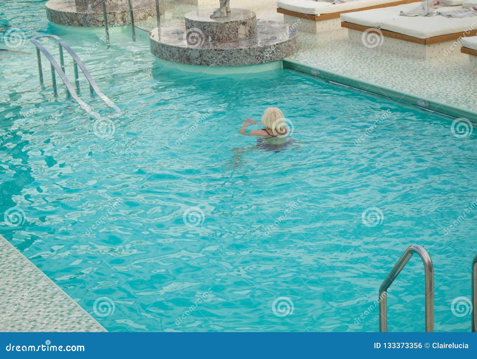 Взрослая белокурая женщина наслаждается поплавать в роскошном бассейне на туристическом судне