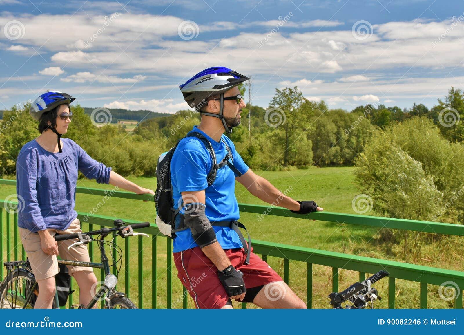 Взрослые пары на велосипедах останавливая на мосте
