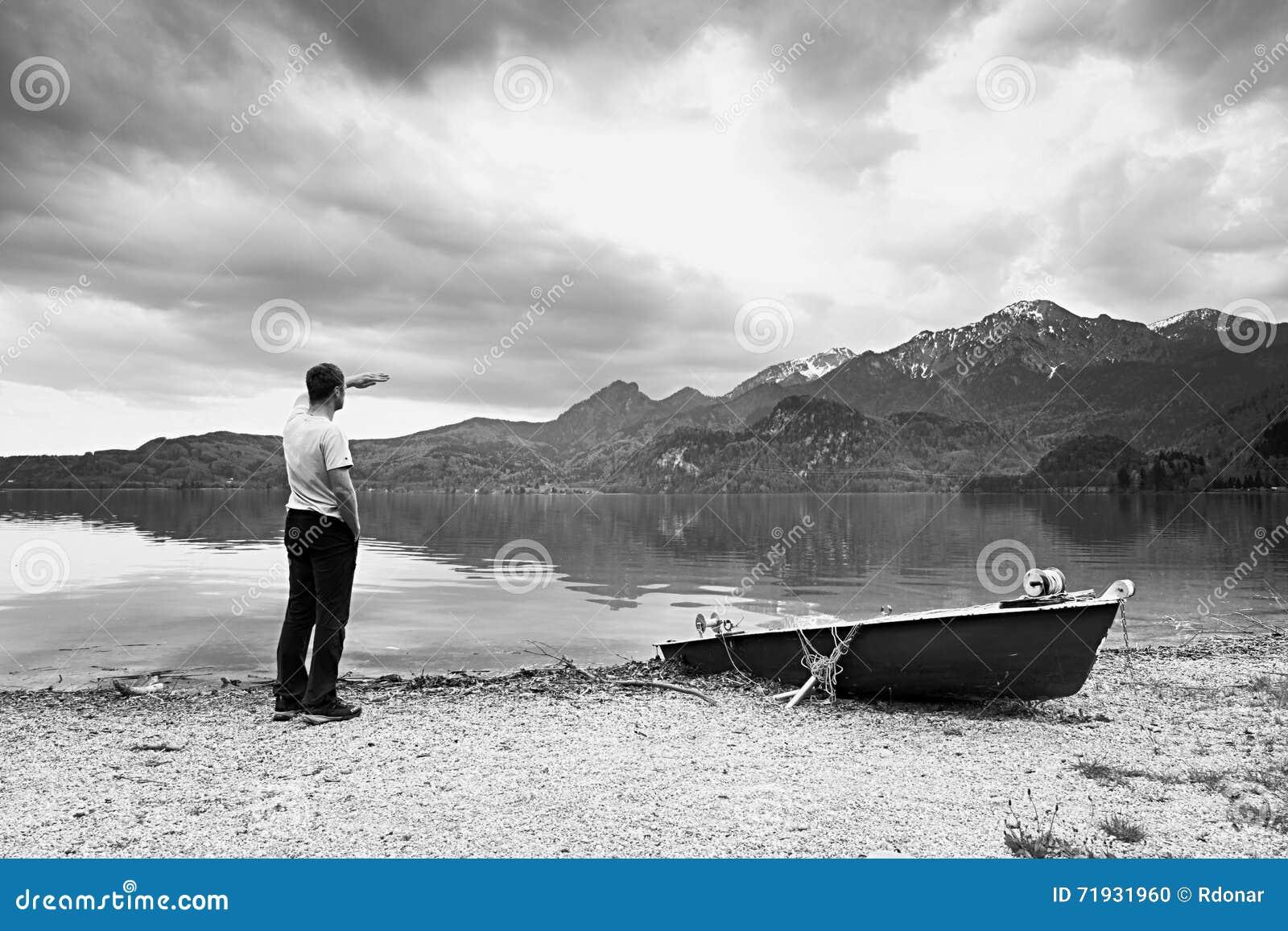 Взрослый человек в голубой прогулке рубашки на старой шлюпке затвора рыбной ловли на побережье озера гор