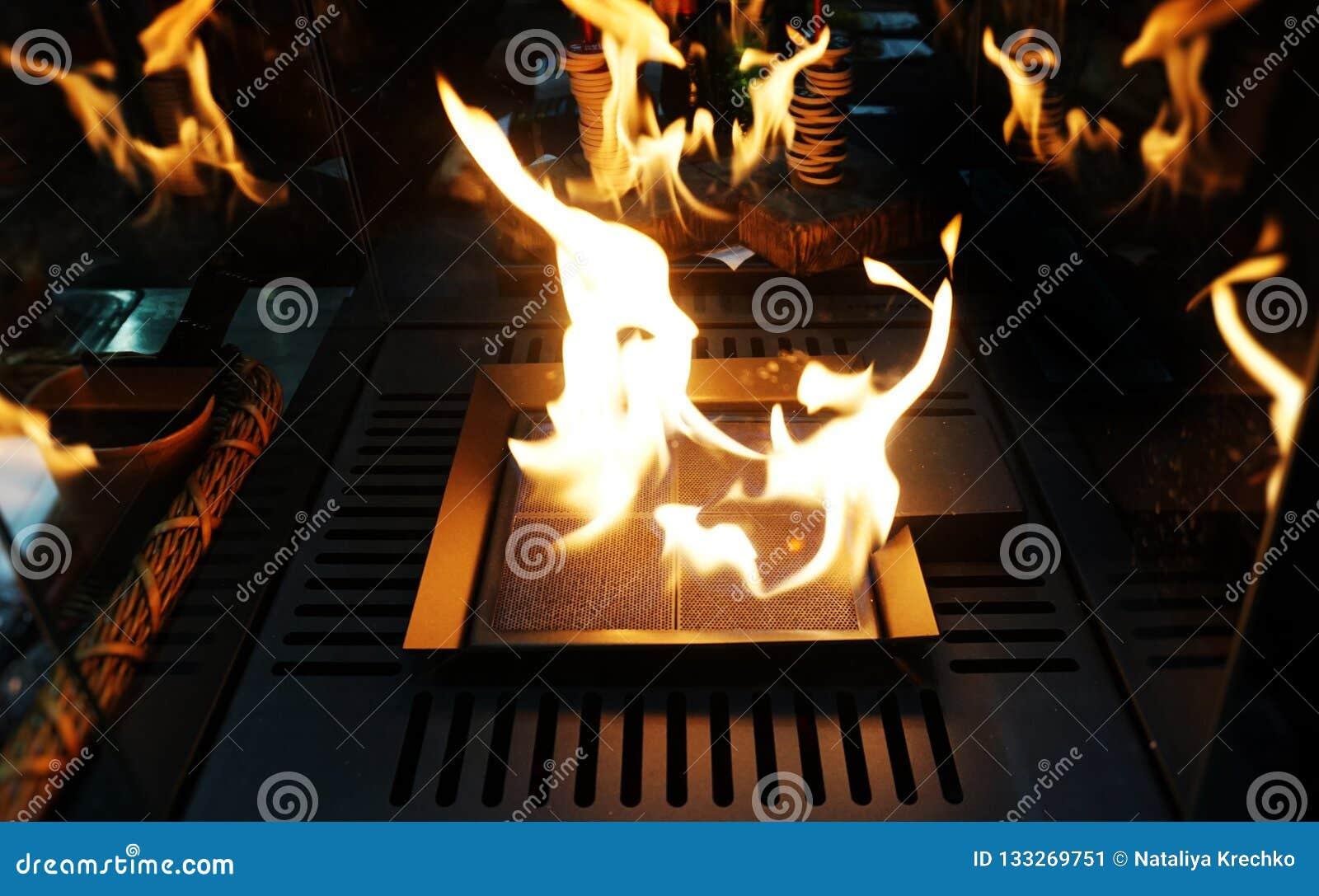 Взрывая предпосылка пламен черная Камин с как раз как огнем горя в кафе