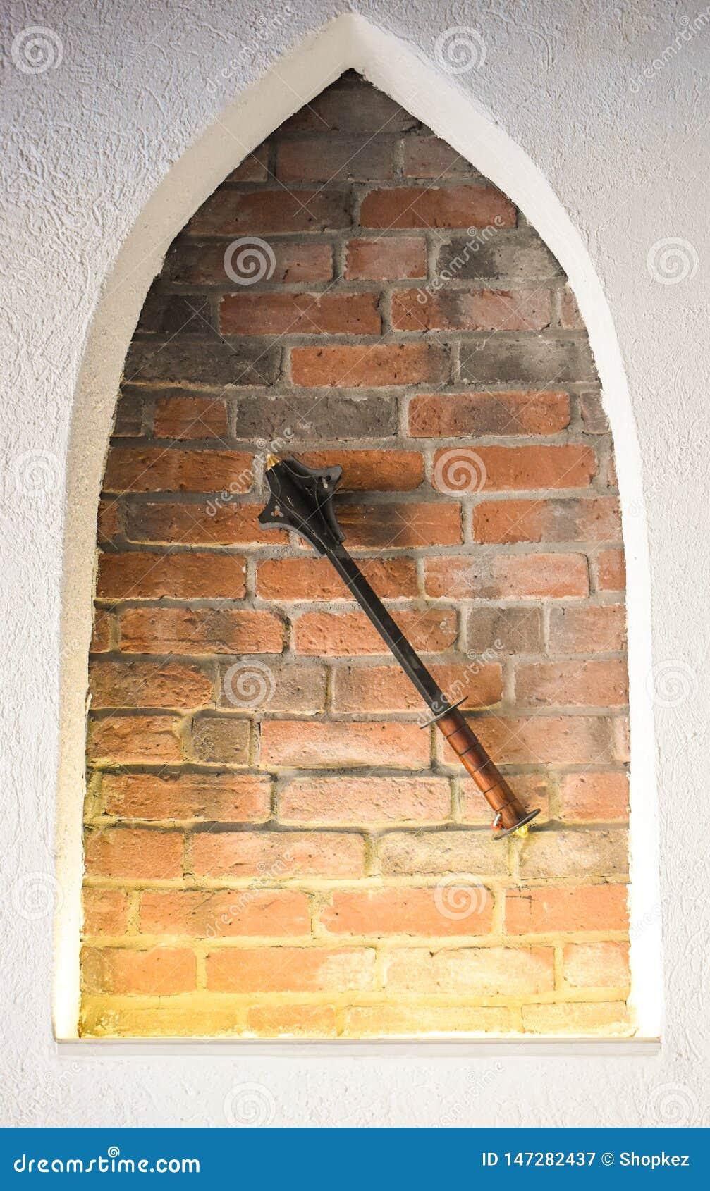 Взятые на острие средневековые утюжат жезл против предпосылки кирпичной стены