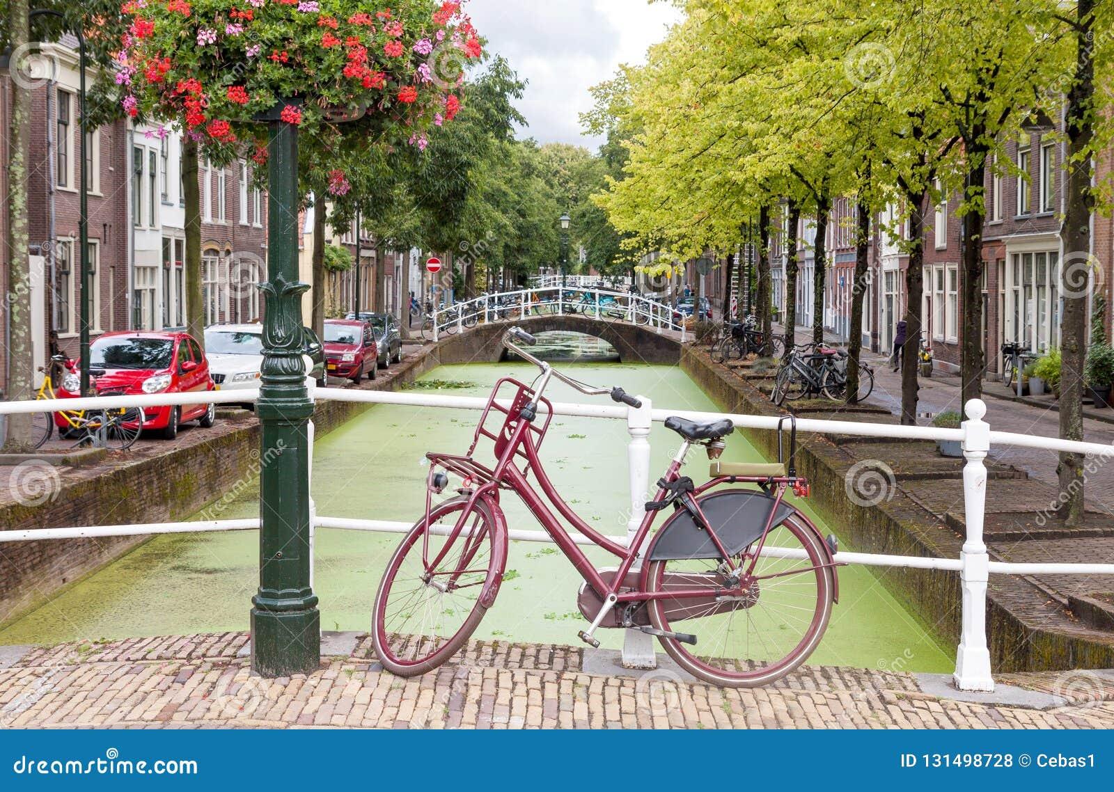 Вид на город Делфта в Нидерланд с каналом воды и винтажным велосипедом
