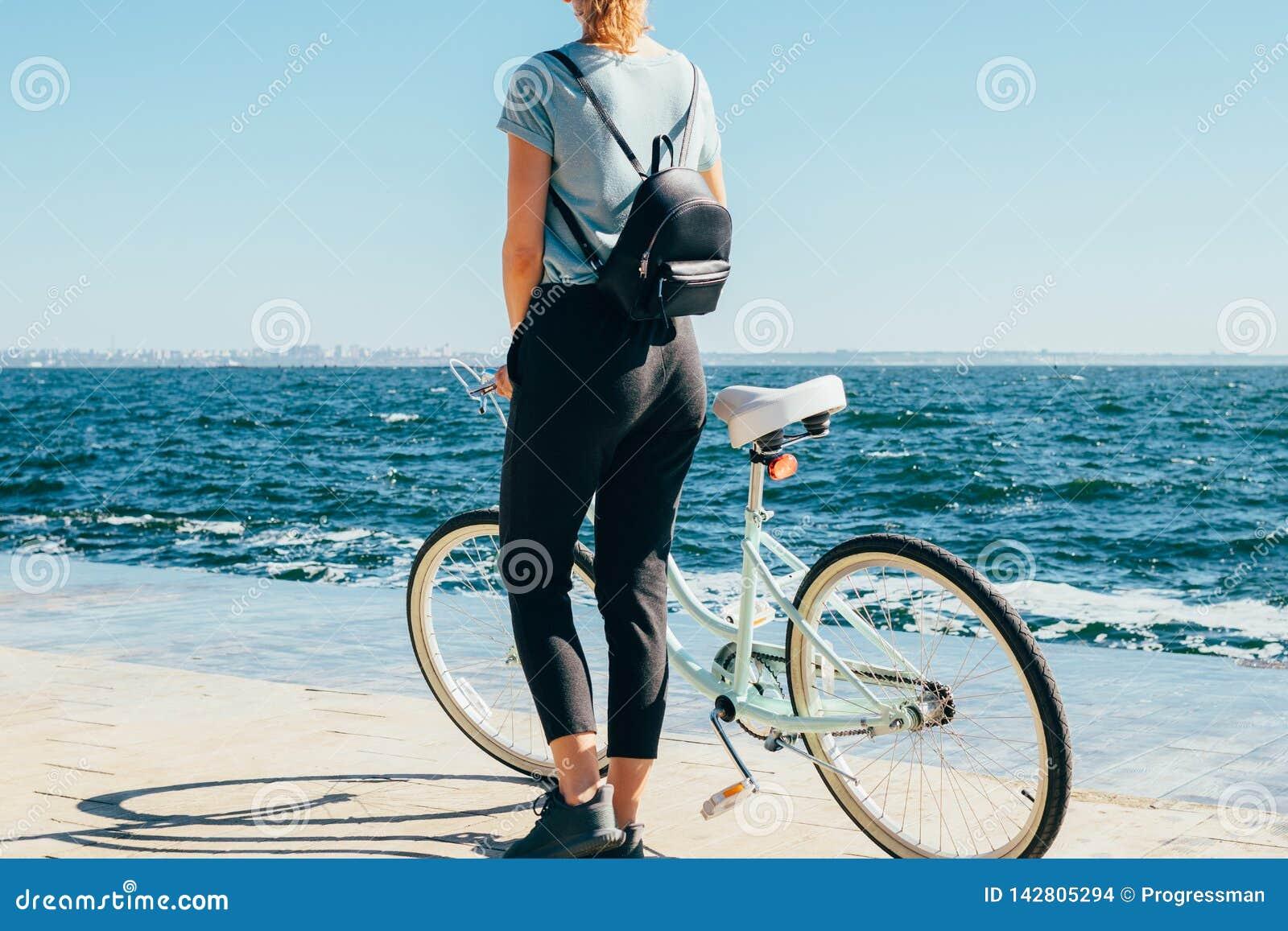 Вид сзади женщины на обваловке на солнечном летнем дне