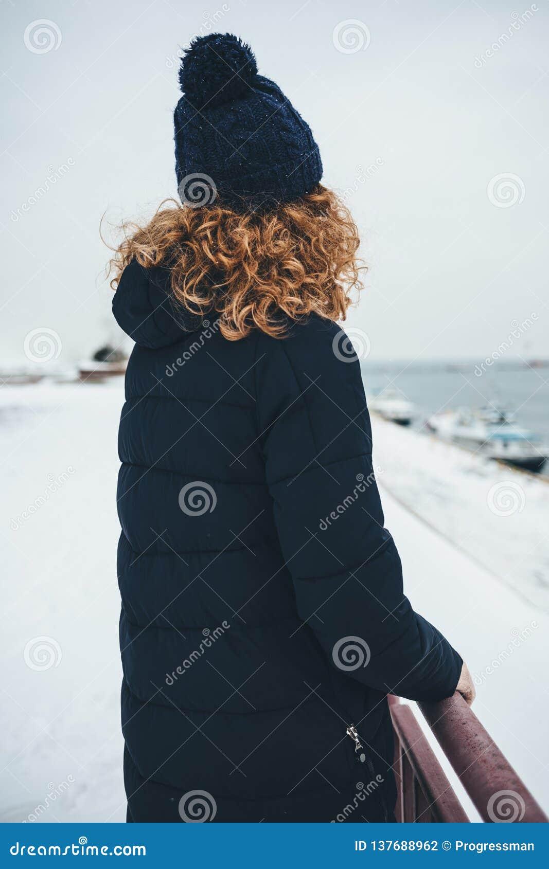 Вид сзади молодой женщины нося теплое пальто