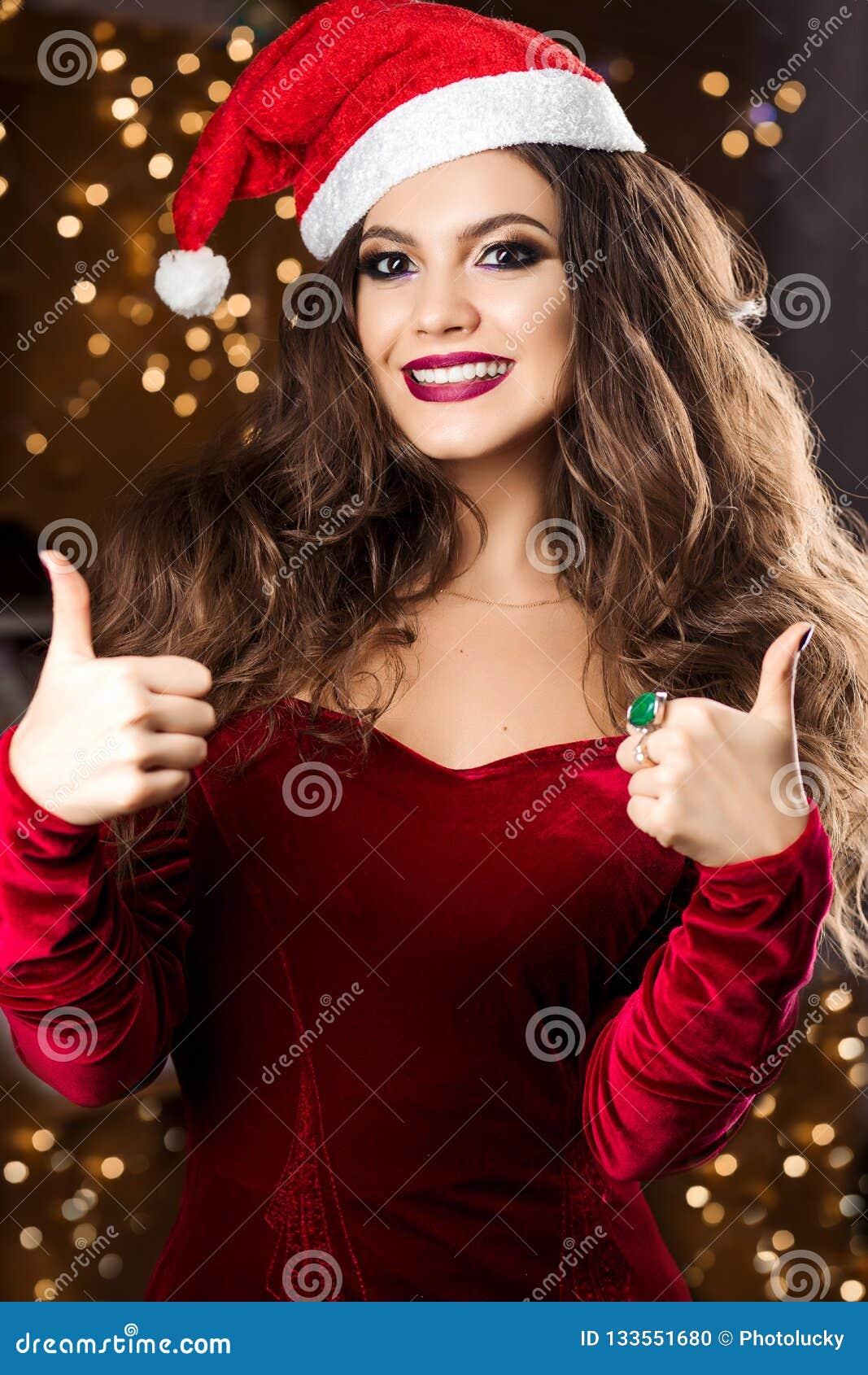 Вид спереди жизнерадостной женщины в знаке показа шляпы santa одобряет