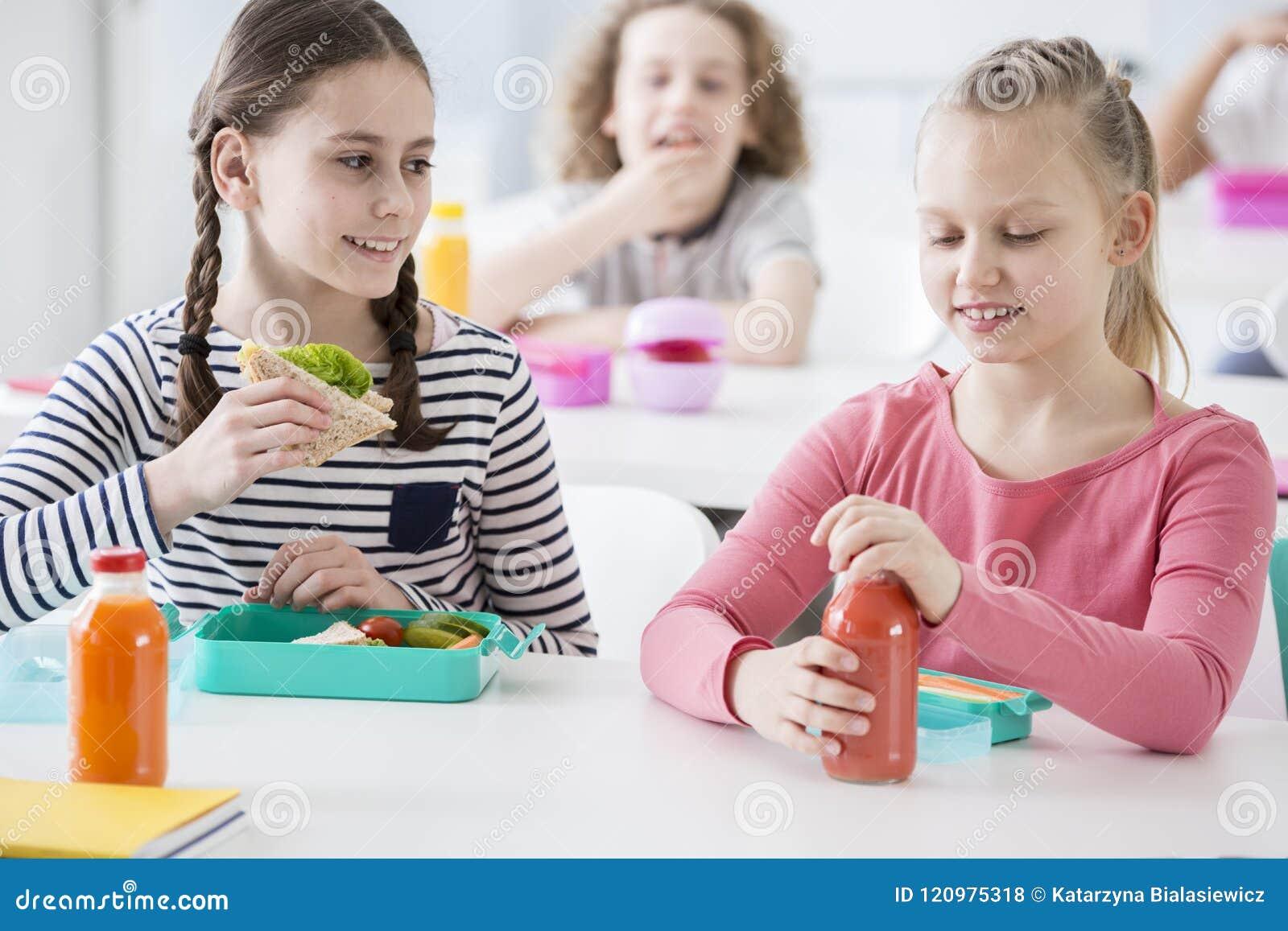 Вид спереди 2 младших девушек в школьном кафетерии во время lunc