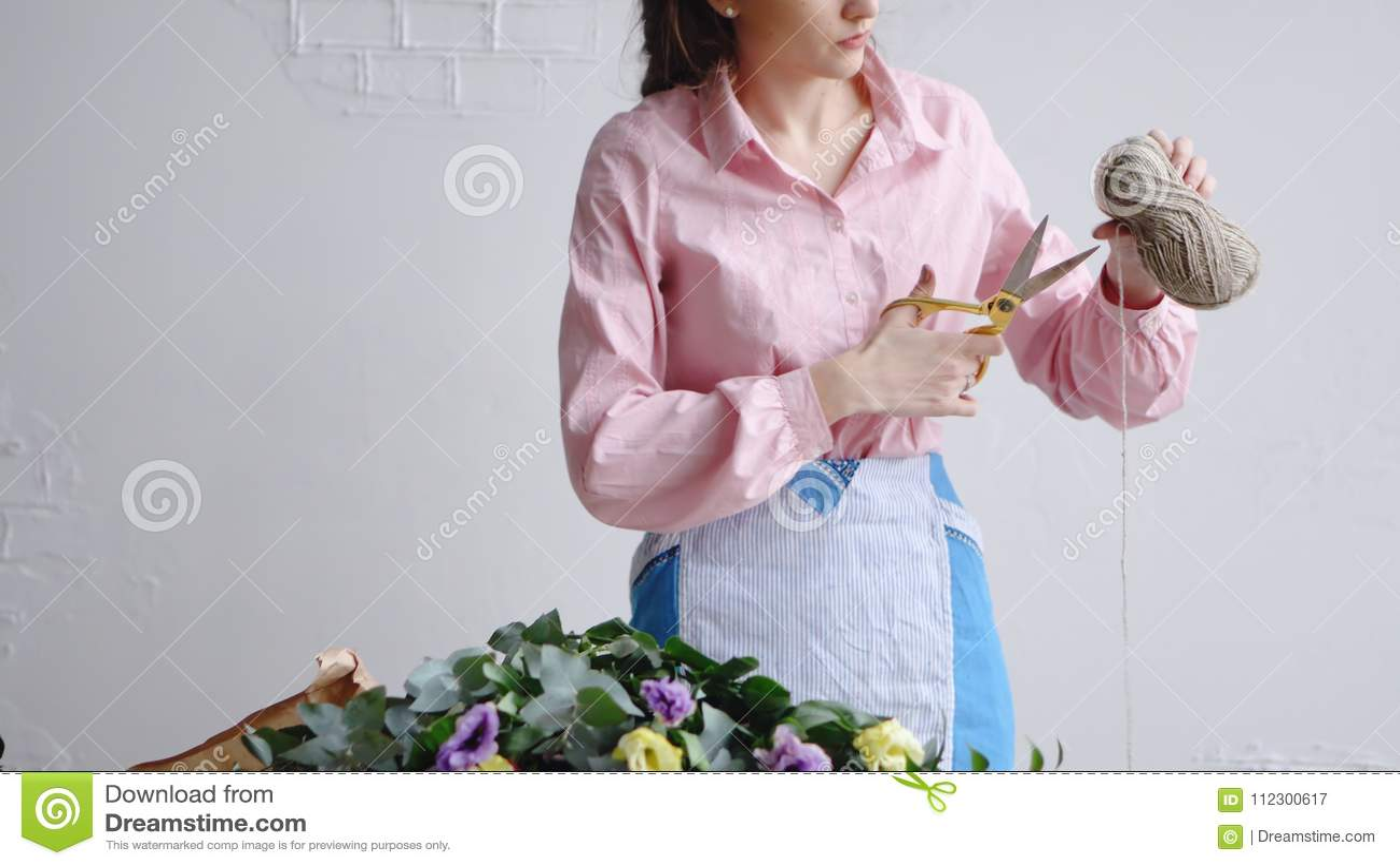 Вид спереди флориста режет поток с ножницами для того чтобы аранжировать букет
