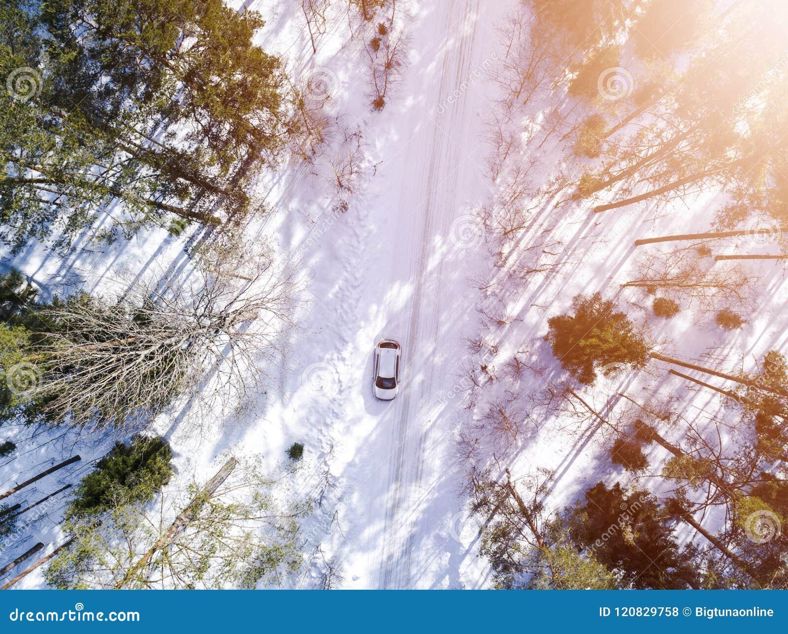 Вид с воздуха автомобиля на дороге зимы Сельская местность ландшафта зимы Воздушное фотографирование снежного леса с автомобилем