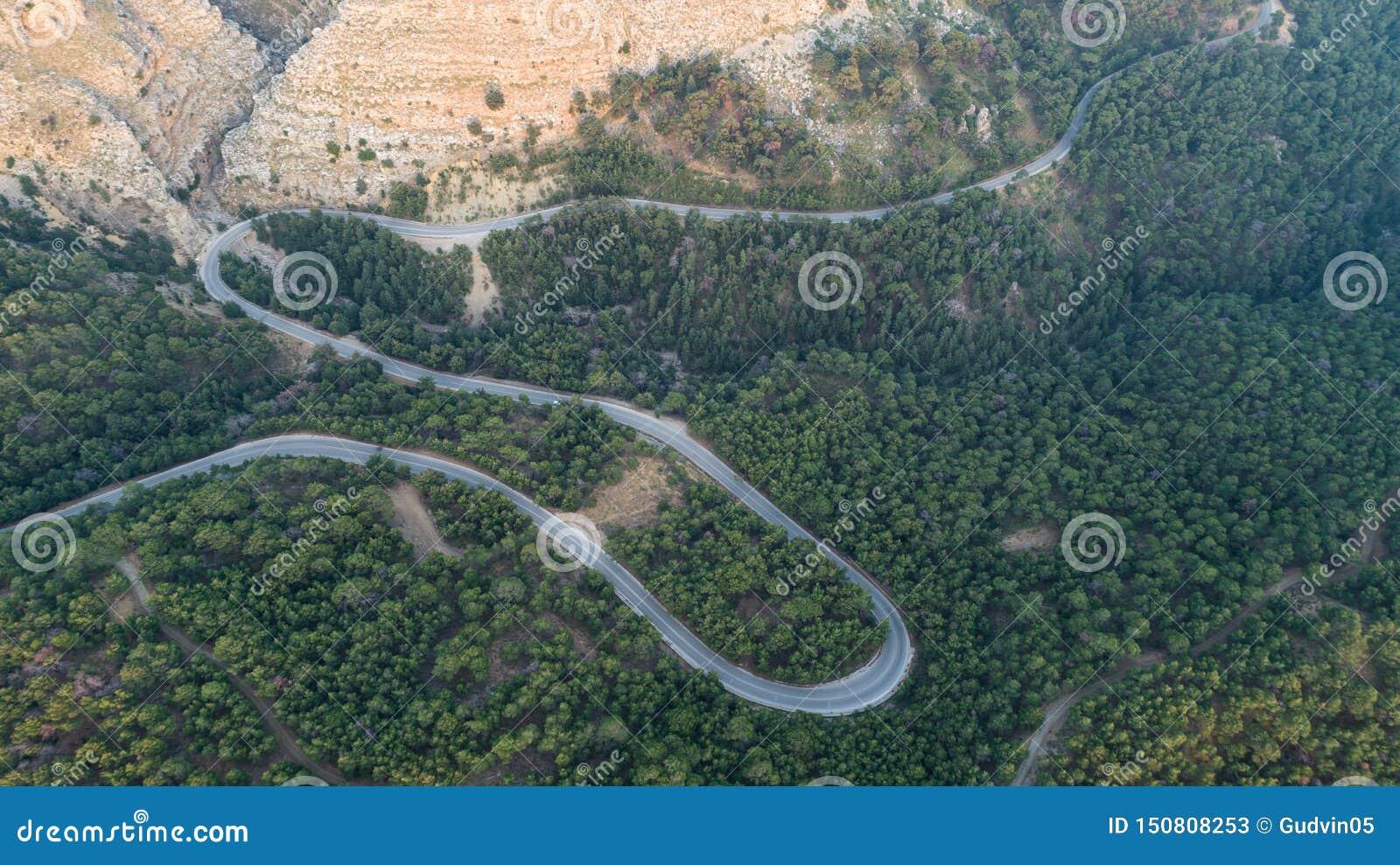 Вид с воздуха дороги кривой горы Зеленый лес на заходе солнца летом в Европе Ландшафт с дорогой асфальта, деревьями на утесах