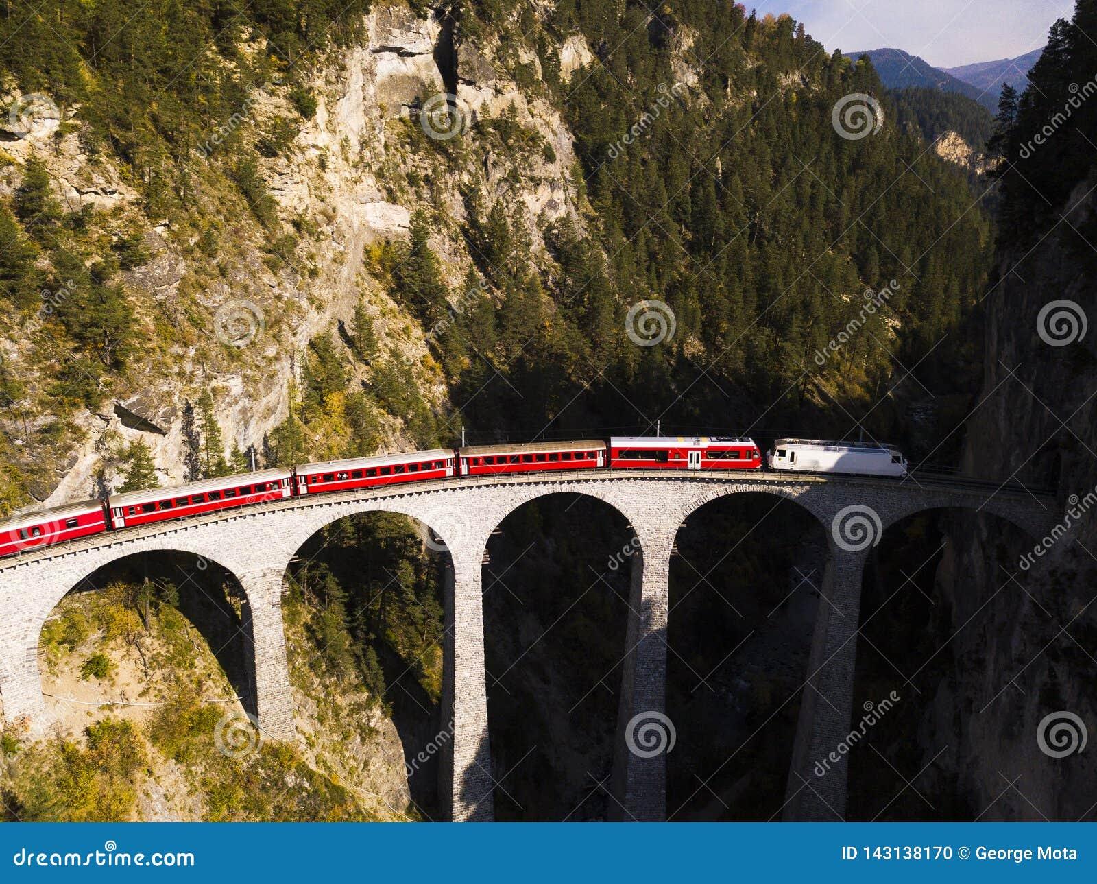 Вид с воздуха красного поезда пересекая виадук Landwasser в швейцарских Альп