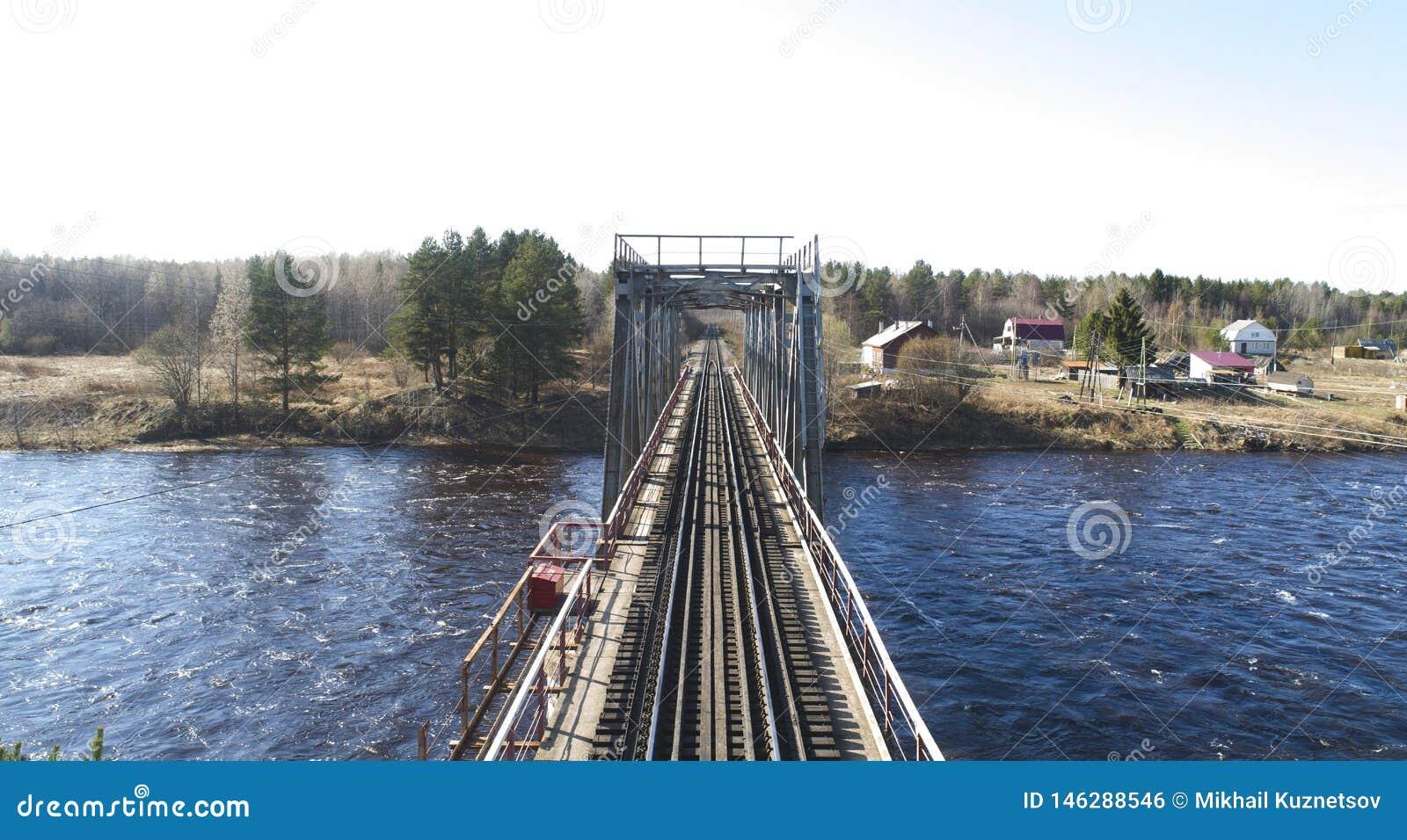 Вид с воздуха на мосте рельса через реку в населенном пункте сельского типа весной