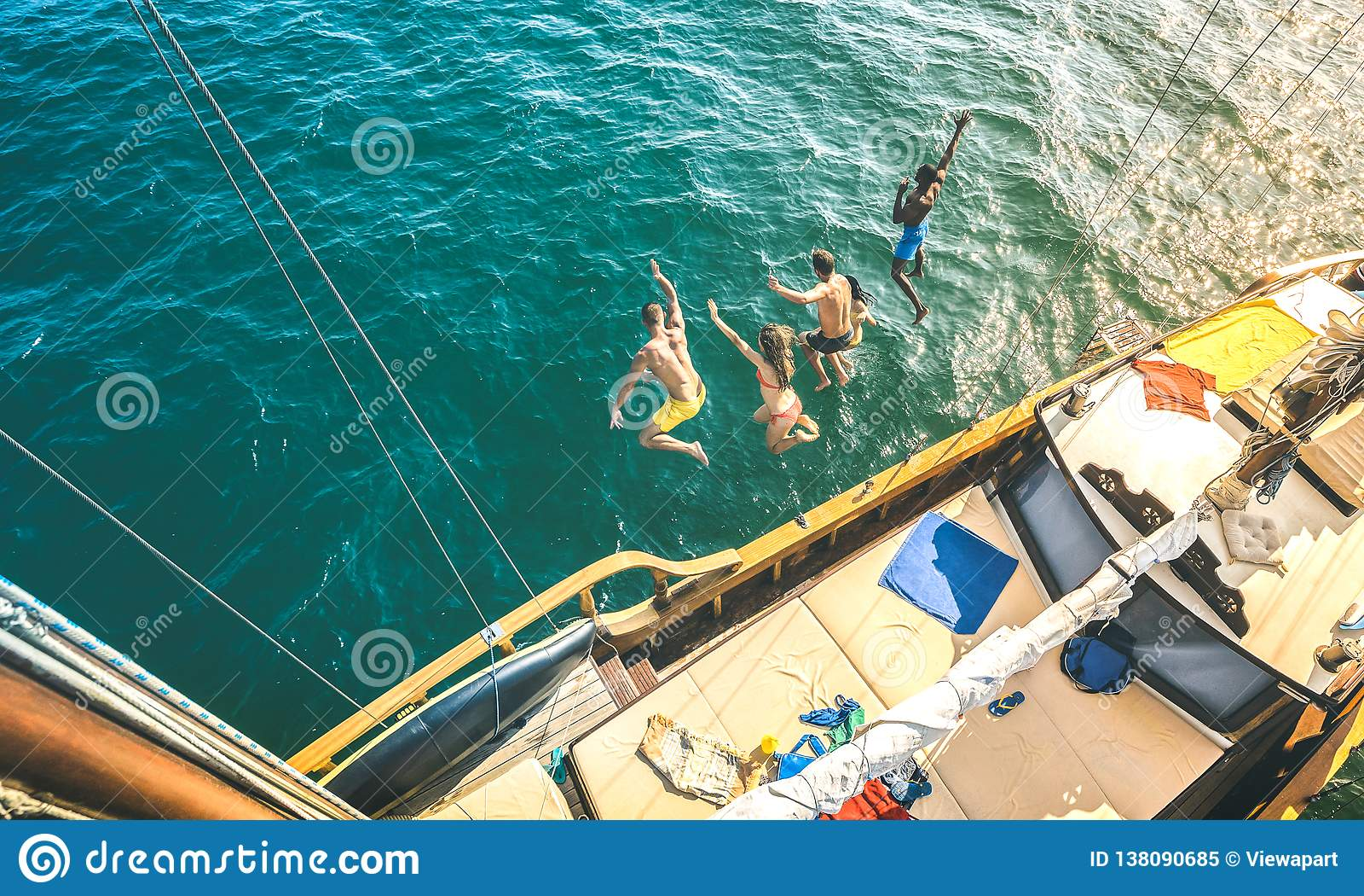 Вид с воздуха счастливых millenial друзей скача от парусника на отключении океана моря - богатые парни и девушки имея потеху совм