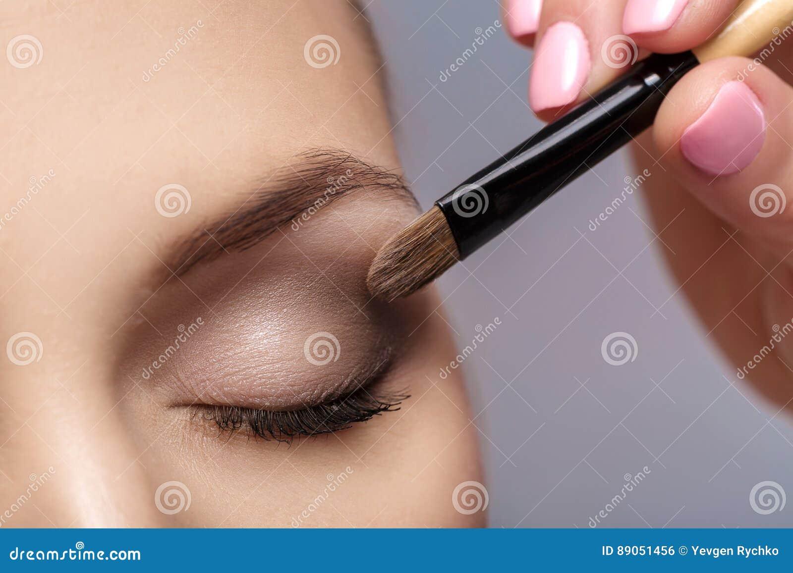 Визажист прикладывает щетку состава для глаз состав для маленькой девочки Тень глаза Брайна конец вверх