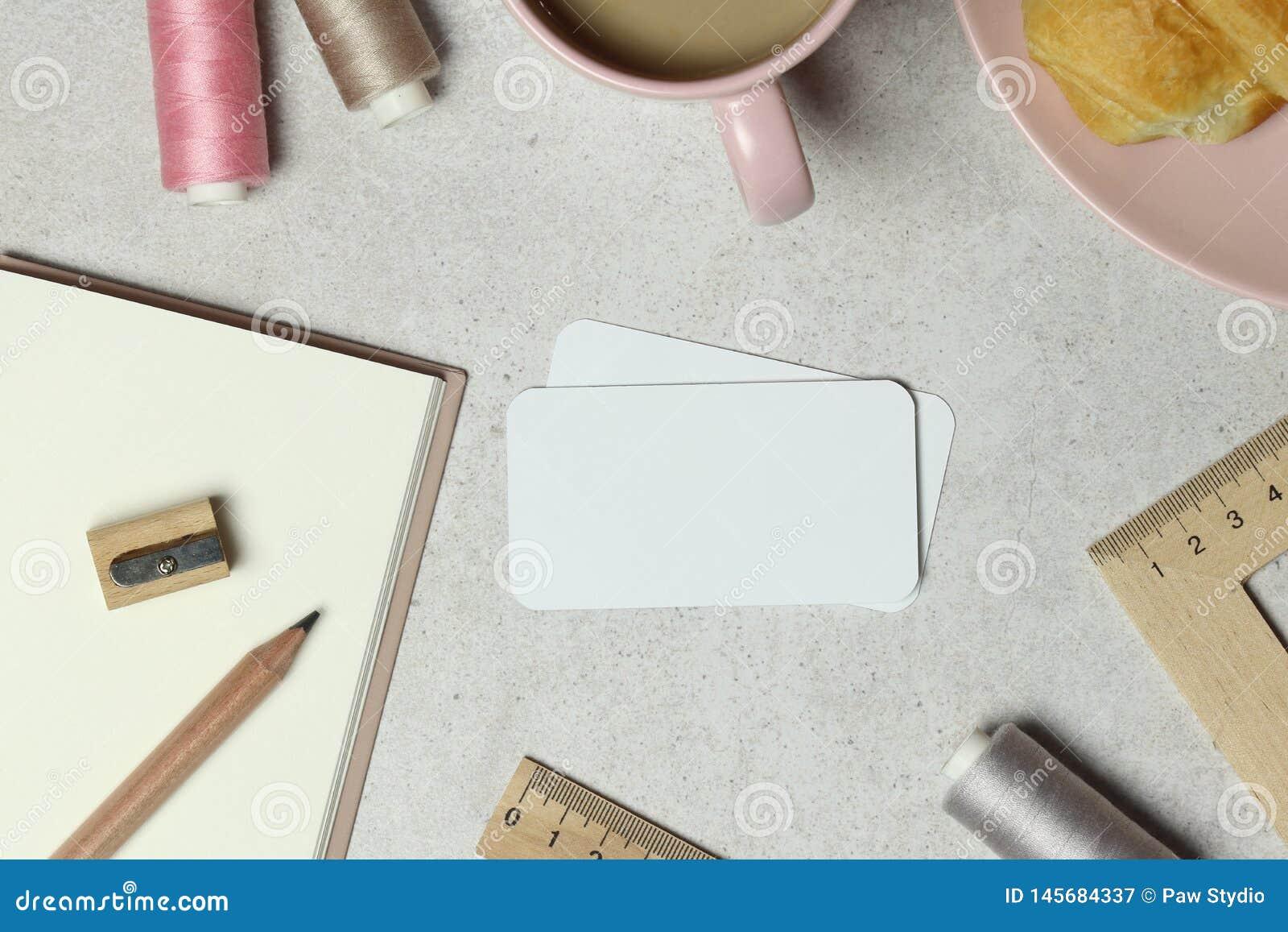Визитная карточка модель-макета на граните с блокнотом, серыми и розовыми потоками, чашкой кофе и тортом, деревянным карандашем,