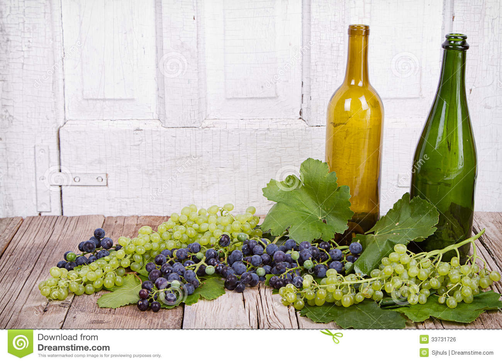 Виноградины и бутылки на деревянной планке
