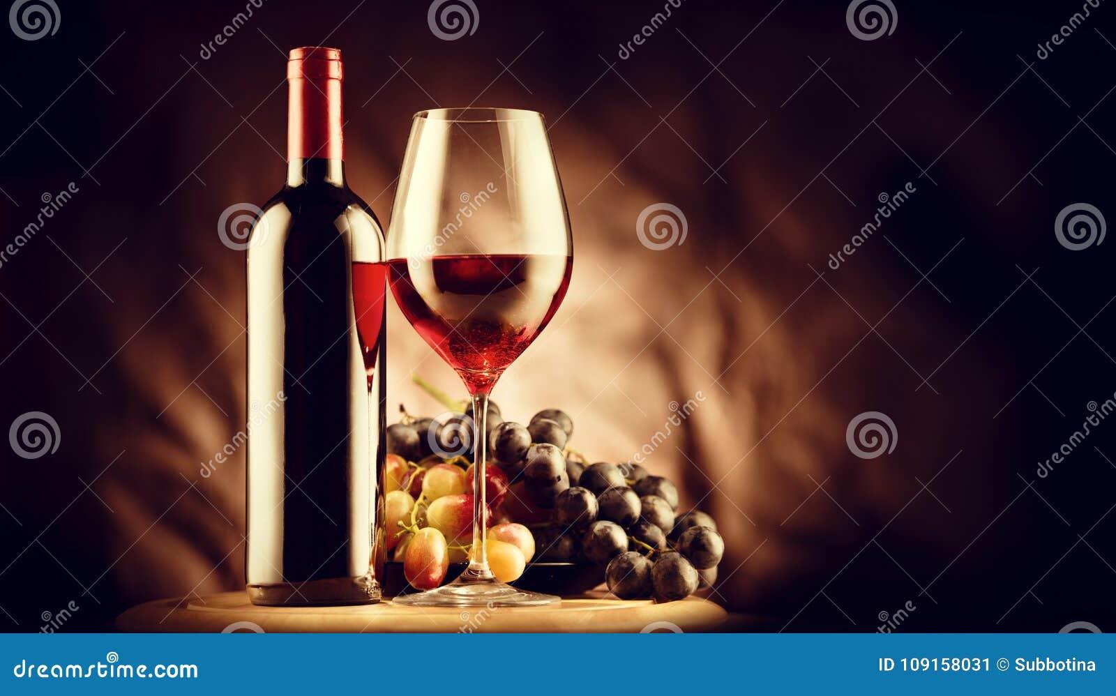 Вино Бутылка и стекло красного вина с зрелыми виноградинами