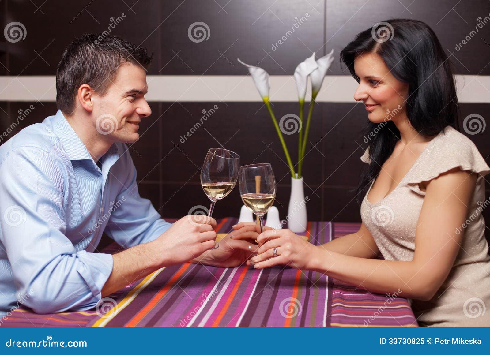 Вино молодых пар выпивая и flirting