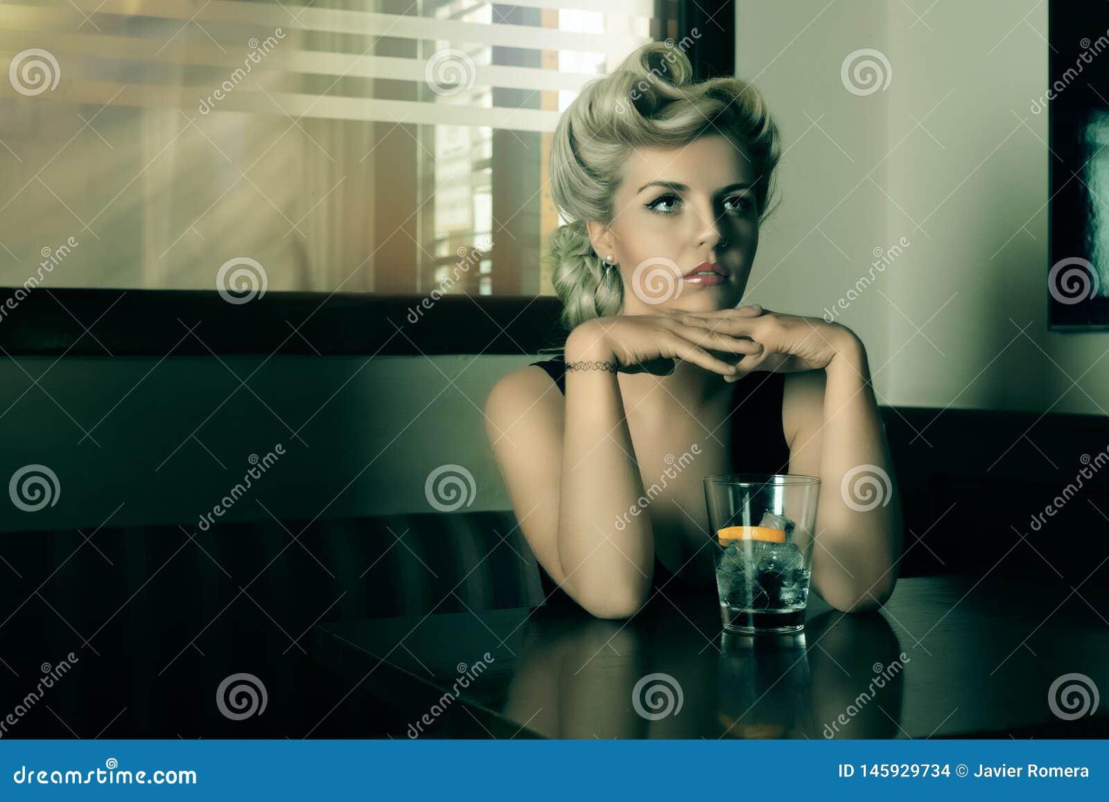 Винтажная и рефлексивная блондинка смотря кто-то в баре