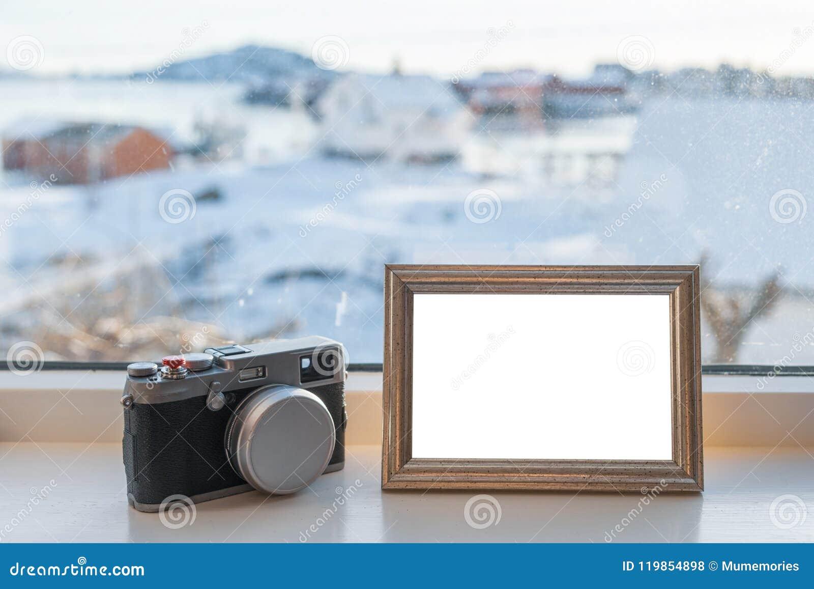 Винтажная камера с пустой картинной рамкой на силле окна