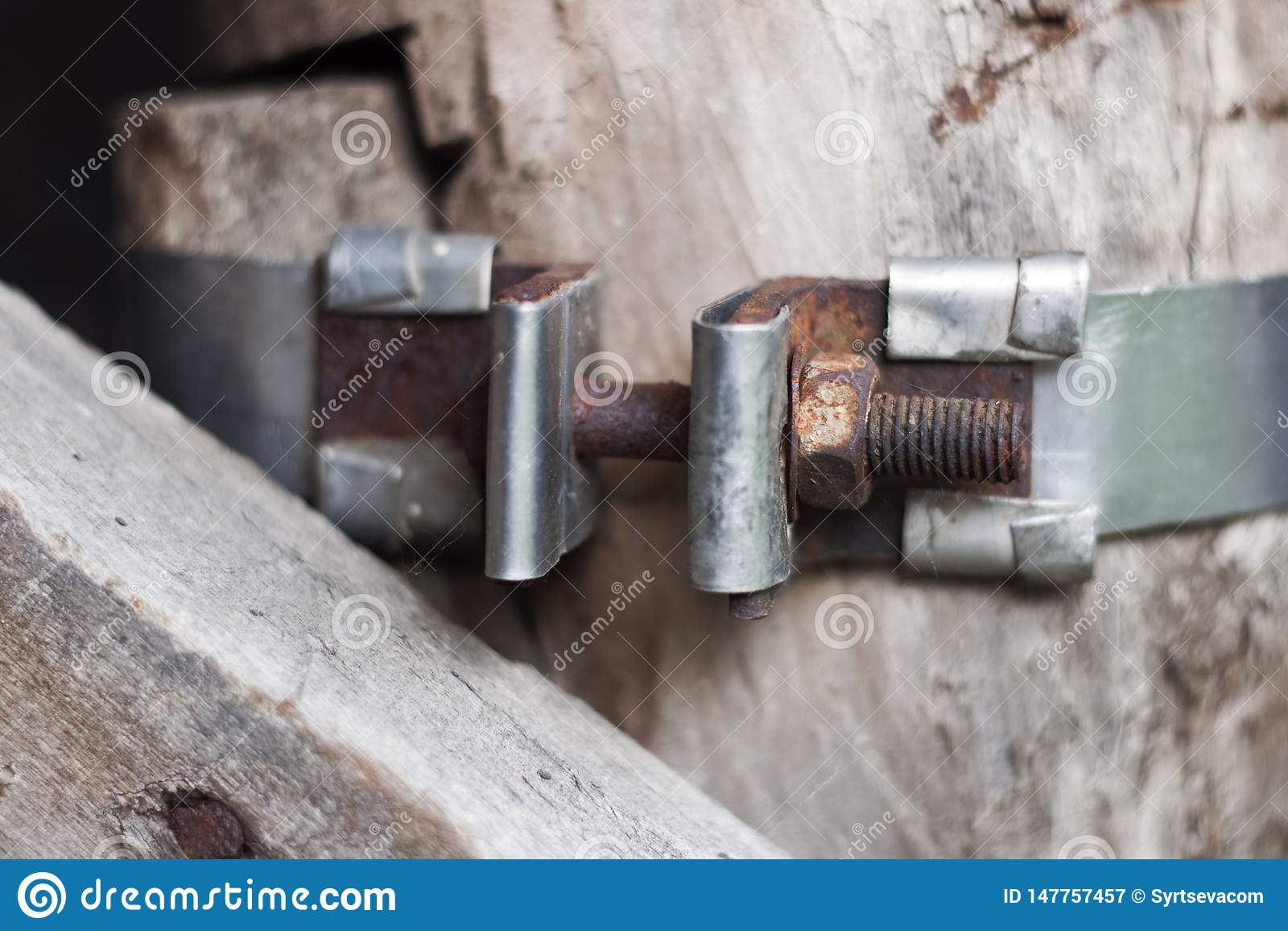 Винтажная часть металла с соединением винта на предпосылке деревянной стены