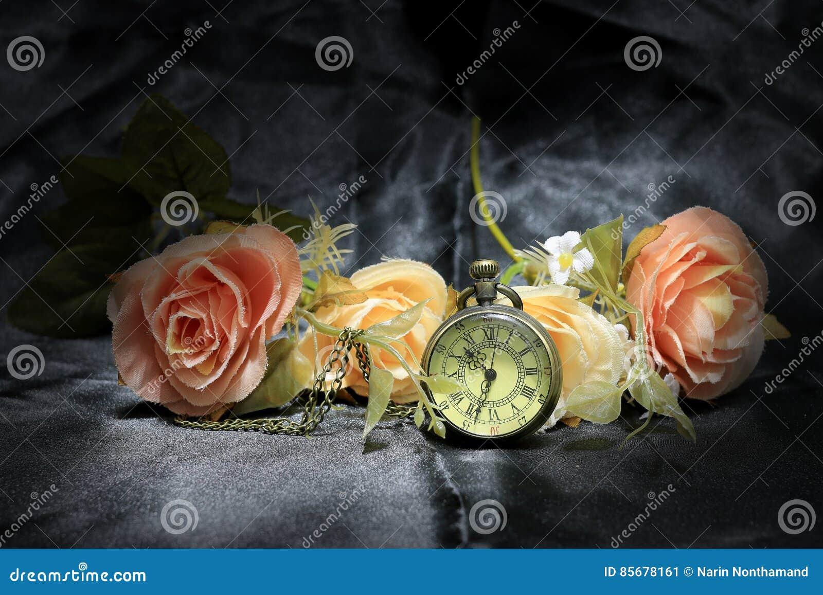 Винтажные карманные часы с розовым цветком на черной предпосылке ткани Влюбленность концепции времени Стиль натюрморта