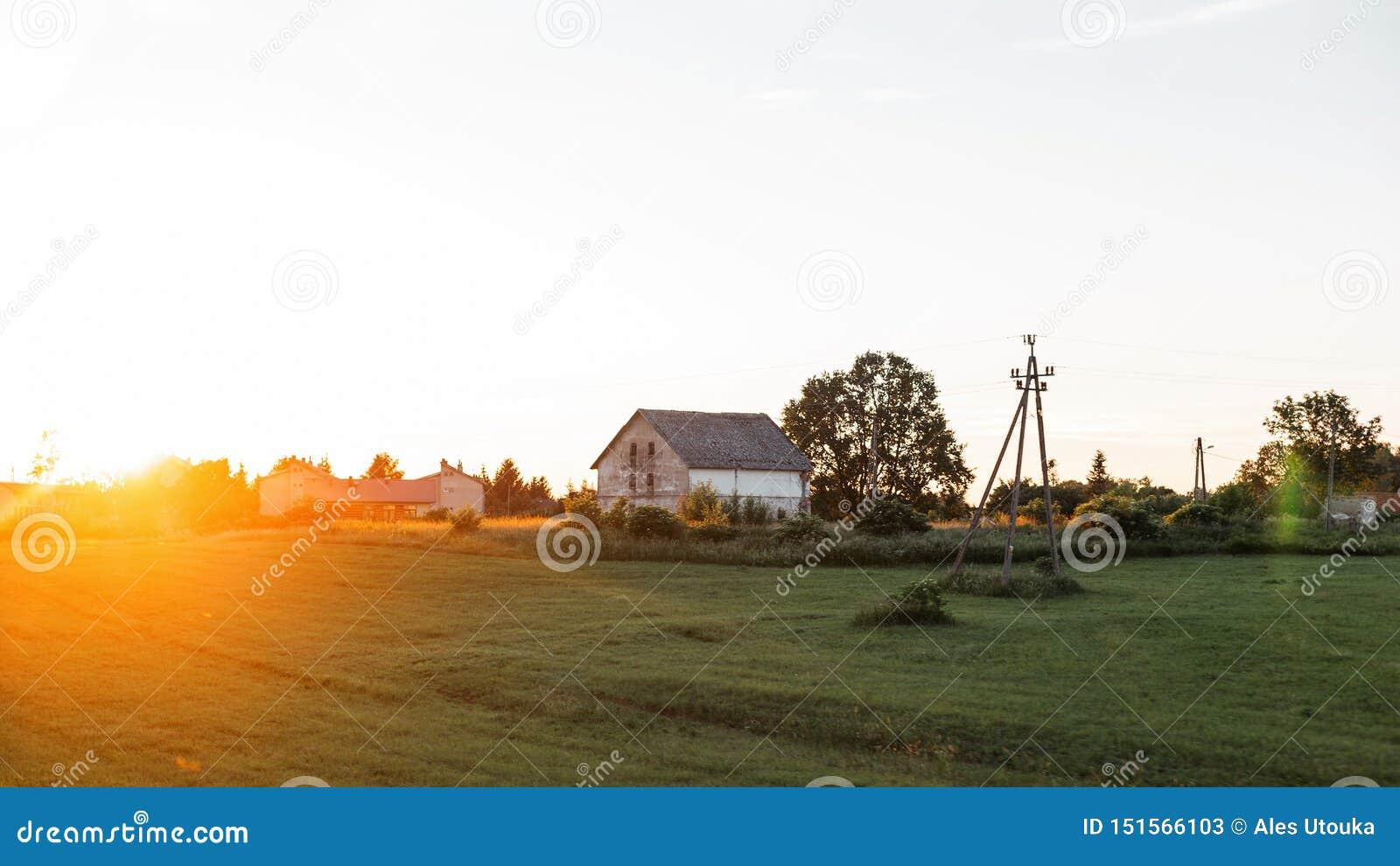 Винтажный Белый Дом в поле в деревне на предпосылке фон яркого оранжевого захода солнца Остатки в сельской местности