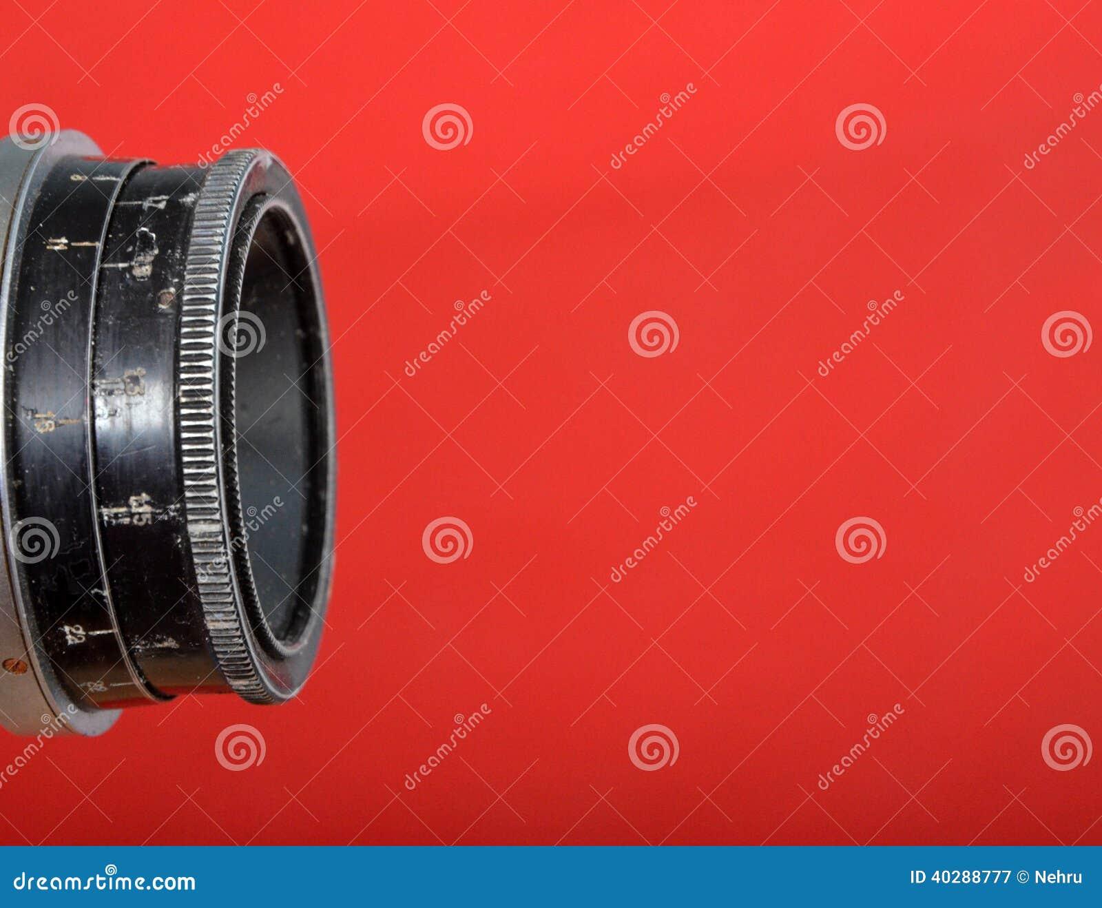 Винтажный объектив на красной предпосылке