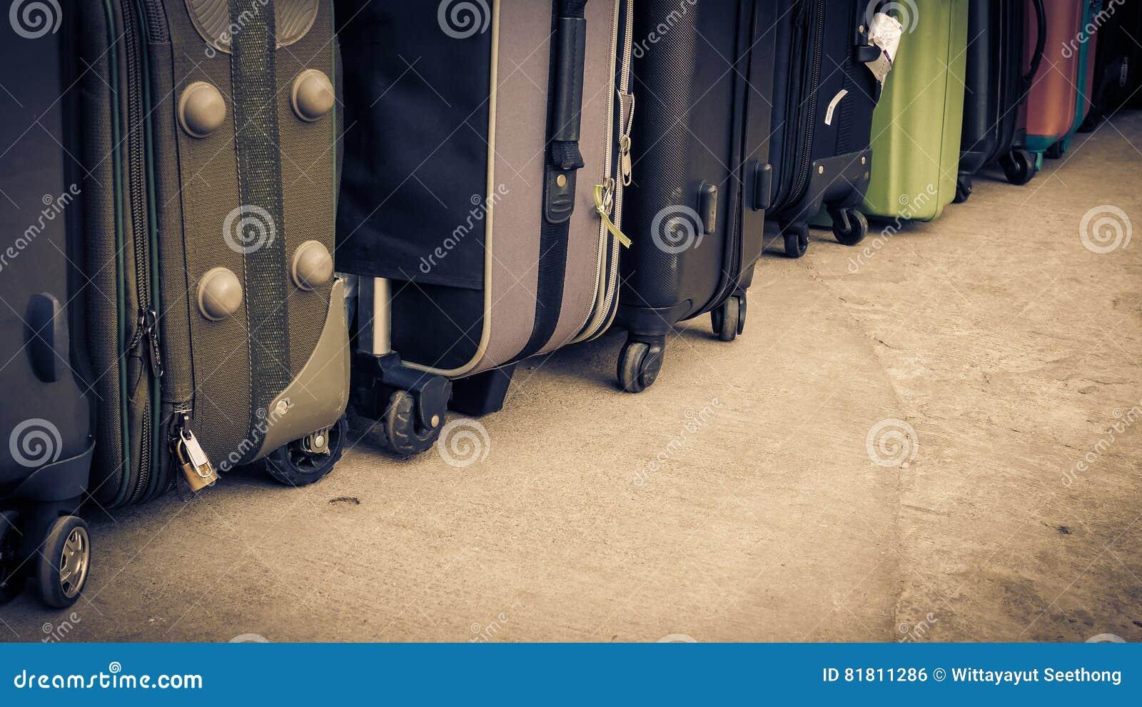 Винтажный стиль сумок или багажа перемещения на поле цемента