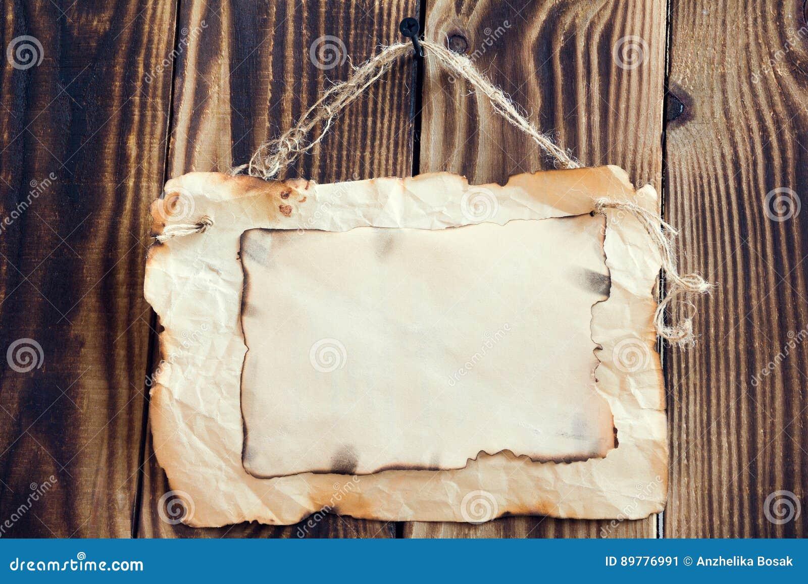 Вися, который палят бумага на деревянной предпосылке