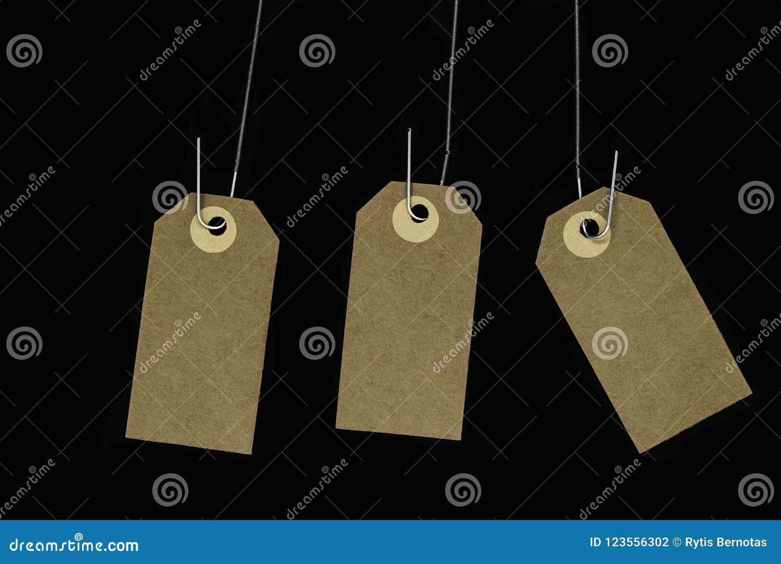 Вися пустые коричневые карточки примечания при космос экземпляра закрепленный на металле скачут и изолировали на черной предпосыл