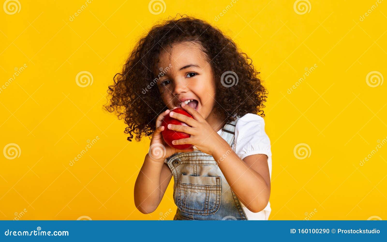 Витамин Маленькая девочка кусает красное яблоко