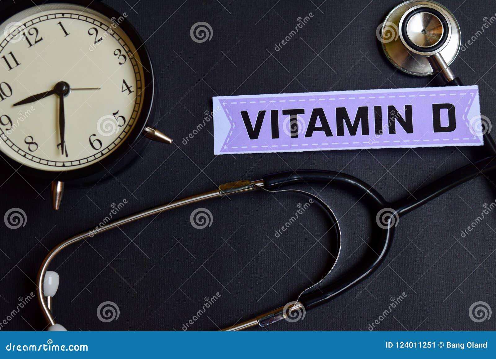 Витамин D на бумаге с воодушевленностью концепции здравоохранения будильник, черный стетоскоп