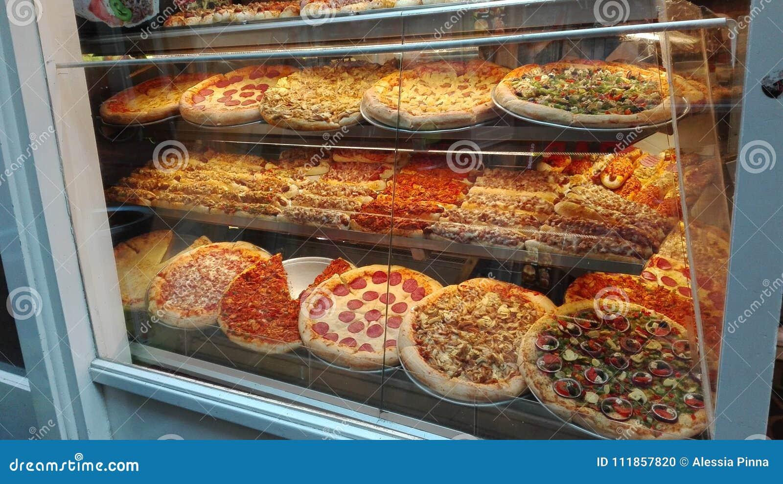 Витрина вполне больших, красочных и заполненных пицц