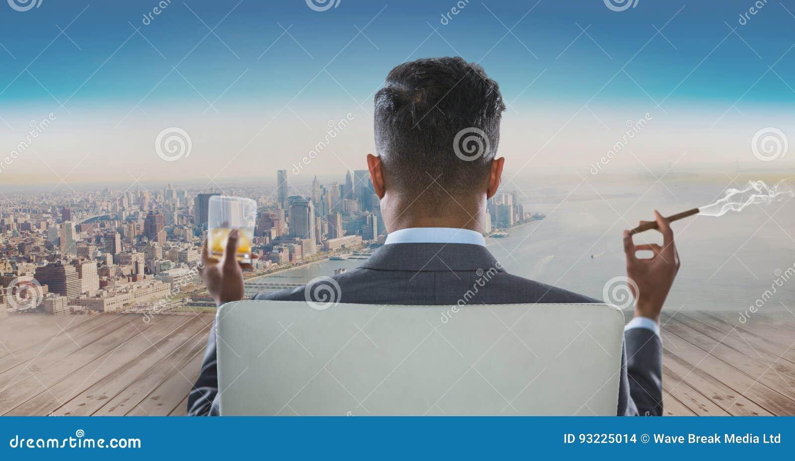 Вид сзади бизнесмена сидя на стуле с стеклом спирта и куря сигары пока смотрящ c