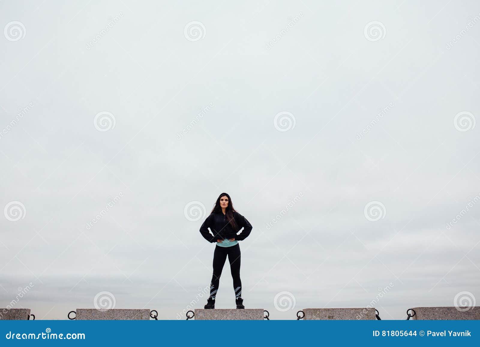 Вид спереди спортсмена после работать стоять на камне гордо и contentedly