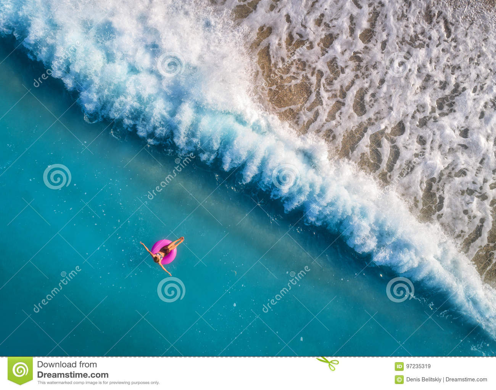 Вид с воздуха заплывания молодой женщины на розовом кольце заплыва