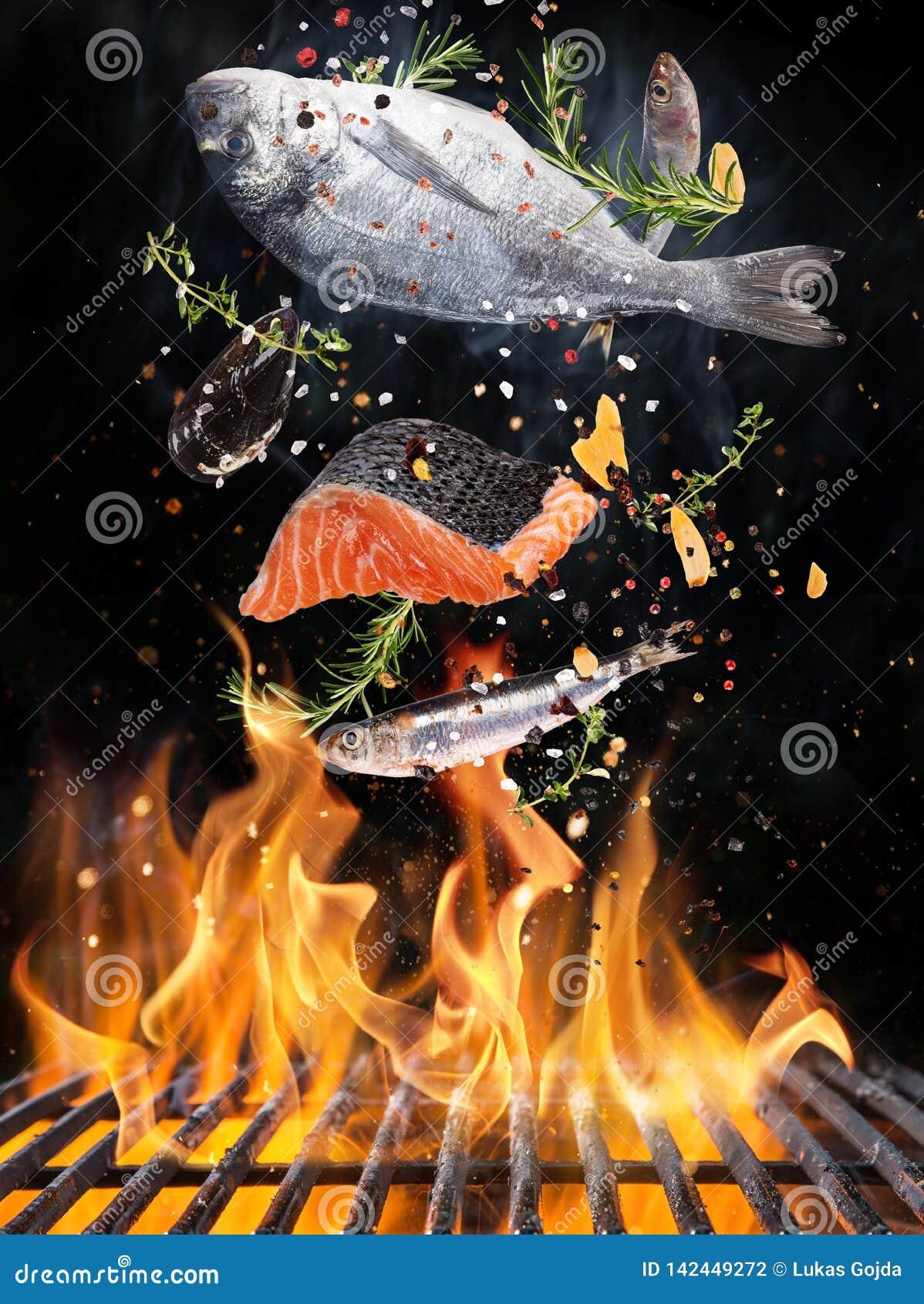 Вкусное летание рыб над решеткой литого железа с пламенами огня