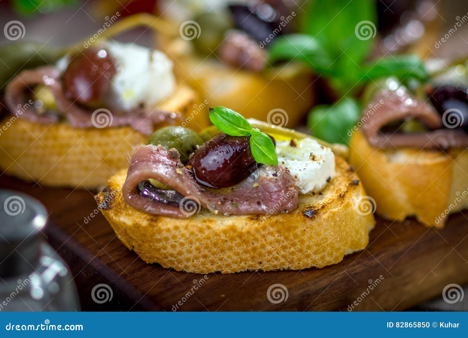Вкусное bruschetta с камсой, каперсами, оливковым маслом