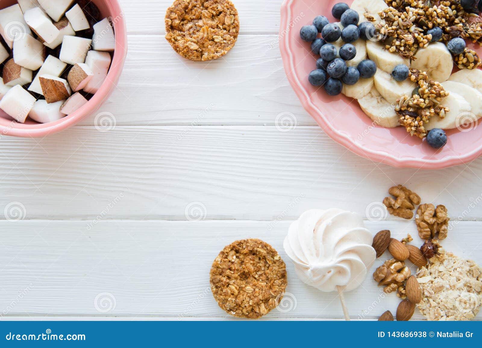 Вкусные закуски на белой таблице, различные виды плодов и печенья, космос экземпляра
