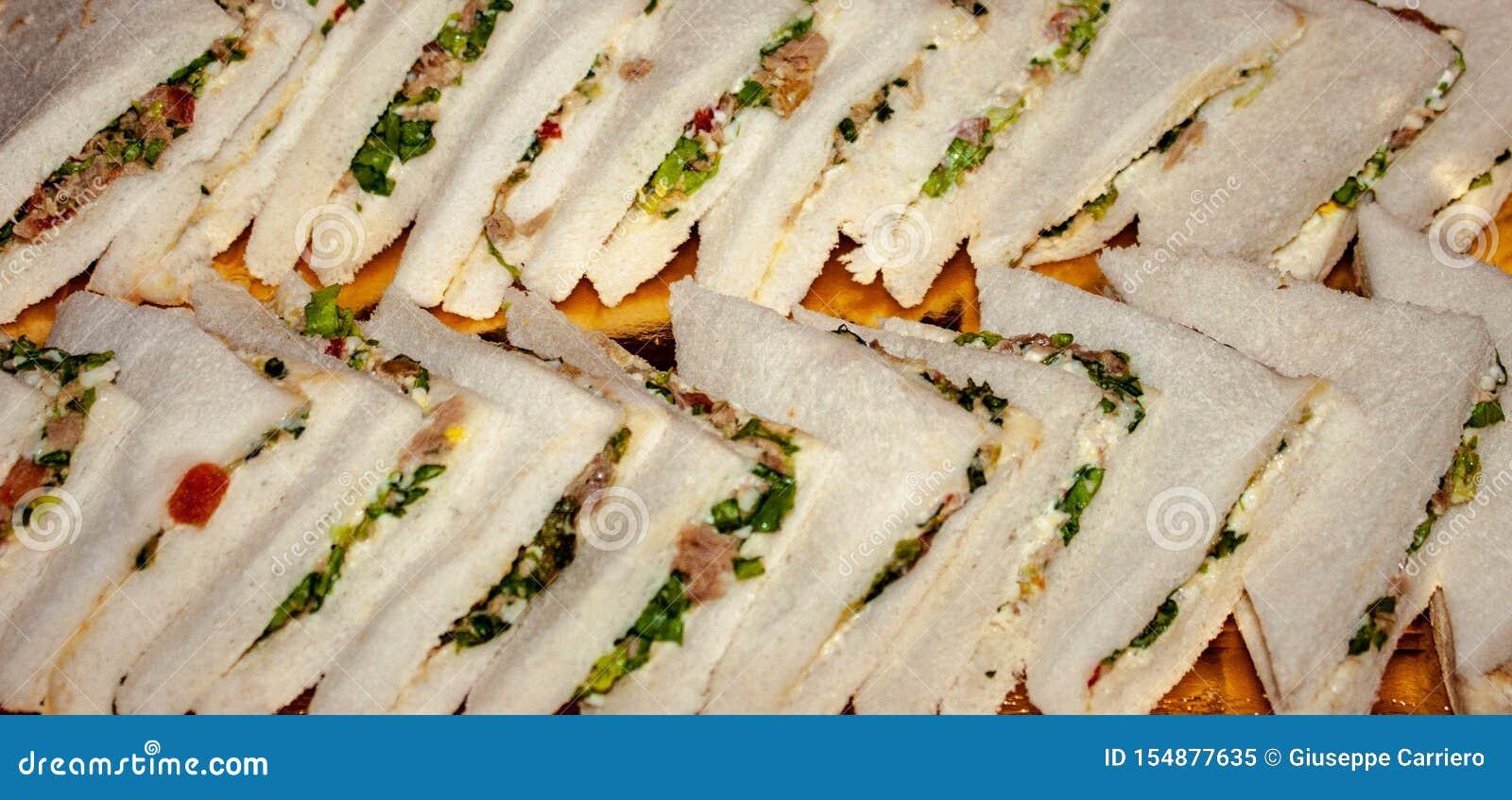 Вкусные сэндвичи подготавливают быть наслаженным, установленный на подносе, сэндвич, хлеб заполненный со что учтено самое лучшее