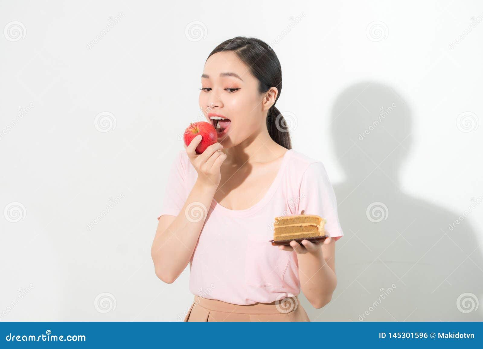 Владения женщины в руке испекут помадку и выбирать плодоовощ яблока, пробуя сопротивляться заманчивости, делает правый диетически