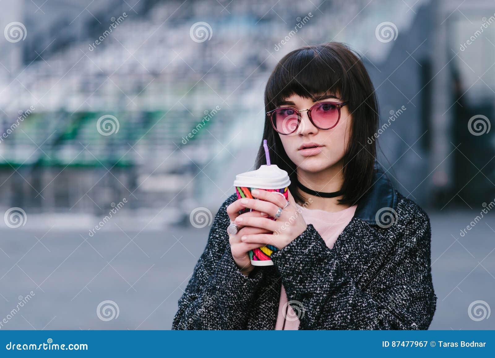 Внешний портрет девушки в розовых стеклах держа красочную чашку горячего питья против