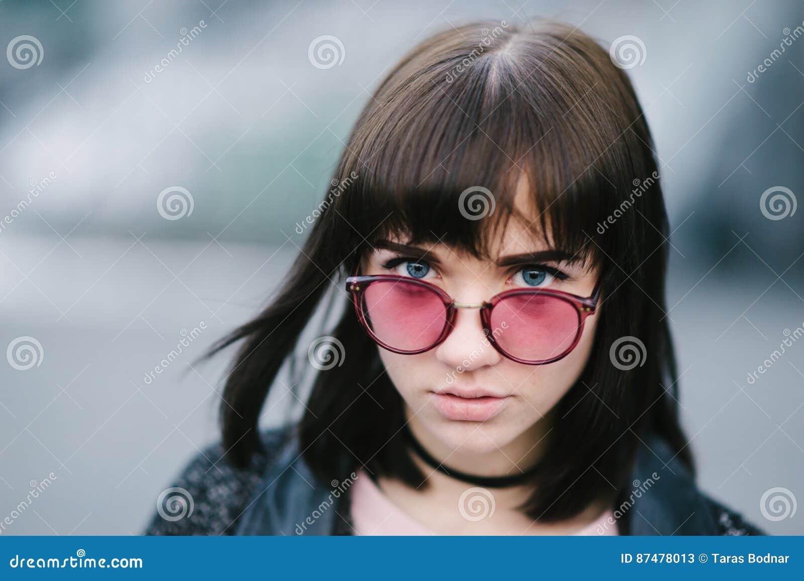 Внешний портрет детеныша и очень красивое брюнет с большими голубыми глазами в розовых стеклах на запачканной предпосылке