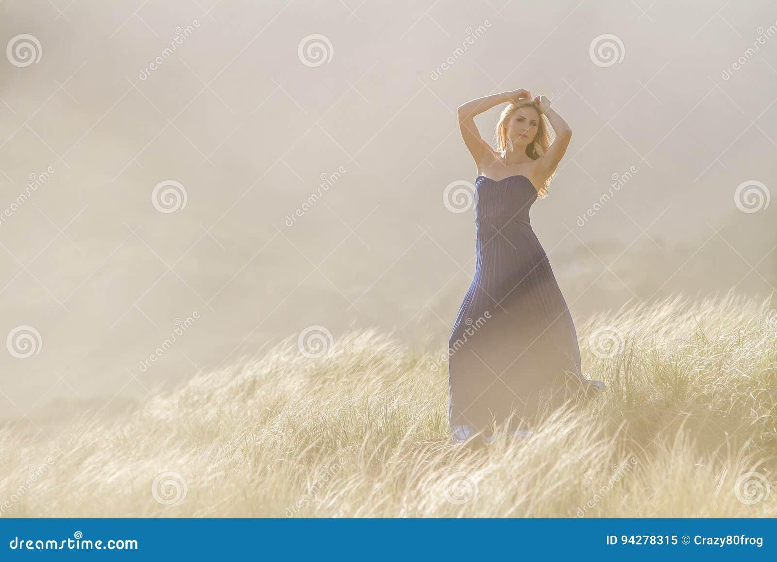 Внешний портрет молодой красивой женщины в голубой мантии представляя дальше