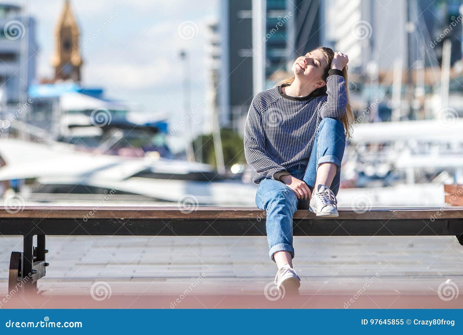 Внешний портрет молодой счастливой усмехаясь предназначенной для подростков девушки на задней части морского пехотинца