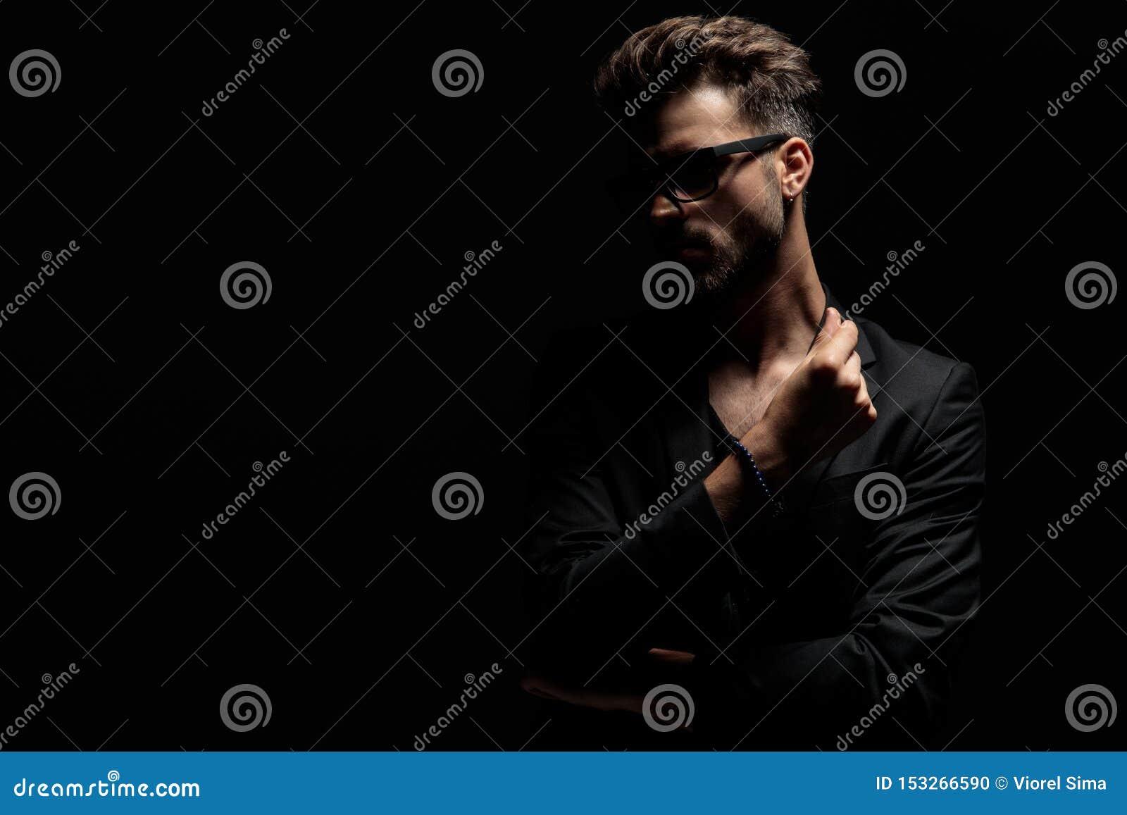 Внимательный загадочный человек смотря прочь и держа его руки сложенный