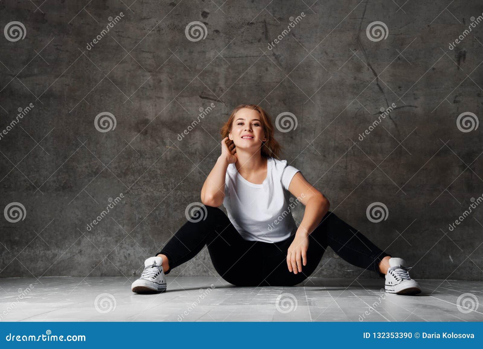 Внушительная женщина со светлыми волосами представляя в рубашке студии нося белой и черных неровных джинсах, сидя на поле